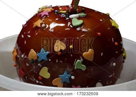 Apple in a caramel glaze. Strew of hearts stars balls. Apple close-up in white plate isolated on white background. Food.
