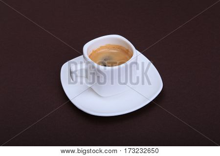 Cup of espresso coffee on white plate, isolated on dark background.