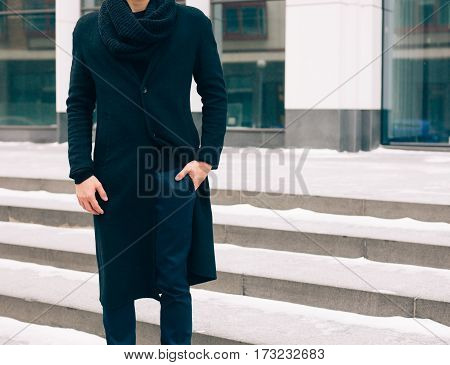 Elegant young handsome business man wearing suit and black coat posing against the background a business building. Fashion and Style. Streetstyle. Part of body.
