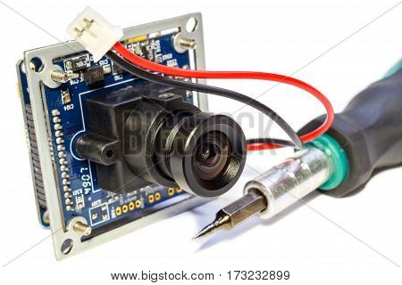 Electronic module with lens for surveillance camera and screwdriver on a white background