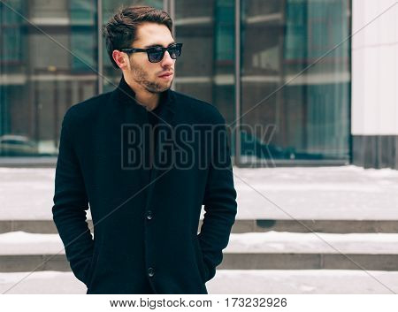 Portrait of young trendy man wearing a black coat with a raised collar in sunglasses. Street style. On the background a business building. Fashion.