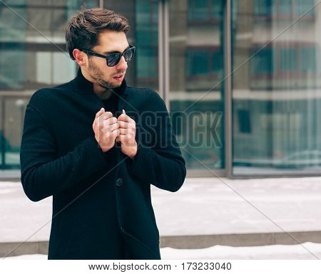 Portrait of young trendy man wearing a black coat with a raised collar in sunglasses. Street style. On the background a business building. Fashion. Close up.