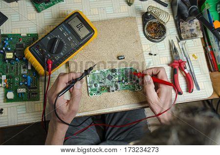 Engineer working with multimeter tools and tweezers. top view
