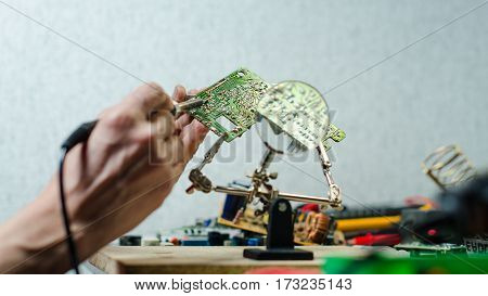 repair electronics chip look through a magnifying glass solderer