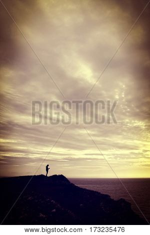 Young woman standing on a cliff looking at her mobile phone