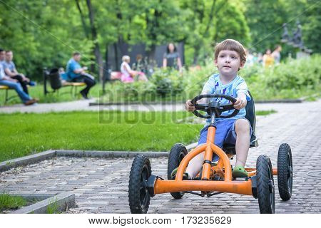 Little Preschool Boy Driving Big Toy Sports Car And Having Fun, Outdoors.