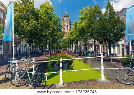 The picturesque Oude Delft canal and leaning tower of Gothic Protestant Oude Kerk church on a sunny day in Delft, South Holland, Netherlands.