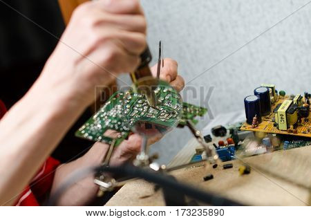 Engineer soldering microcircuit though magnifier. third hand tools
