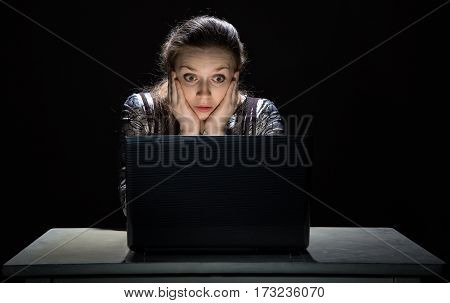 Scared woman watching interesting movie on black background
