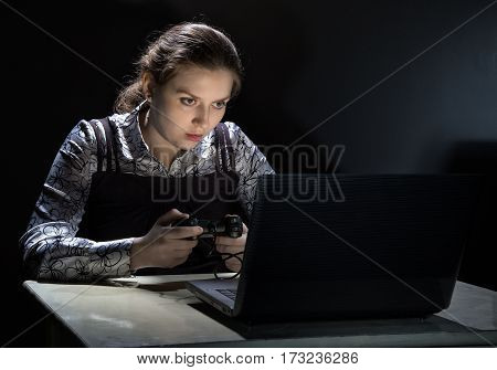 Tired woman playing video games on black background