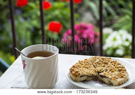 A cup of tea with lemon and a pie from shortcake dough on the table on terrace with flowerbed background