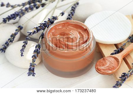 Cosmetic red clay mask mixed in jar, dried lavender flower twigs on white stones.
