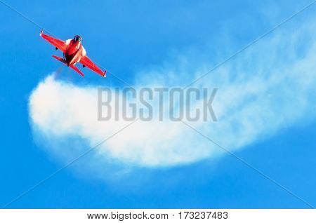 Red fighter jet in the blue sky with white smoke trail