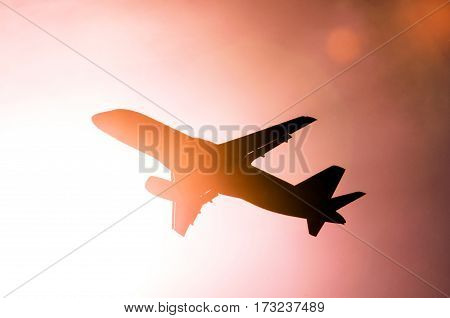 Passenger airplane on a background of abstract pink sky bright sun glare