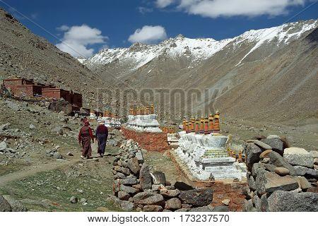 Two Tibetan pilgrim lady go to the monastery Driraphuk Gompa along 108 Buddhist stupas on the slope of Sacred Mount Kailash in Western Tibet.