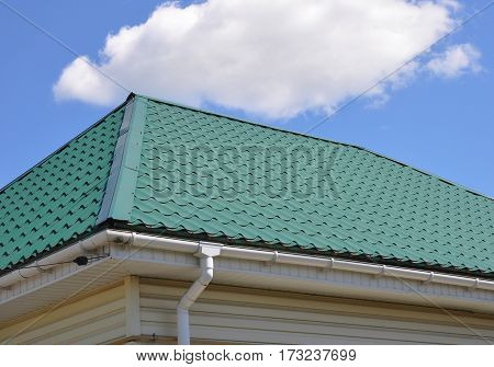 Green Metal Roof and Rain Gutter System with Downspout Pipe House Exterior. Roofing Construction.