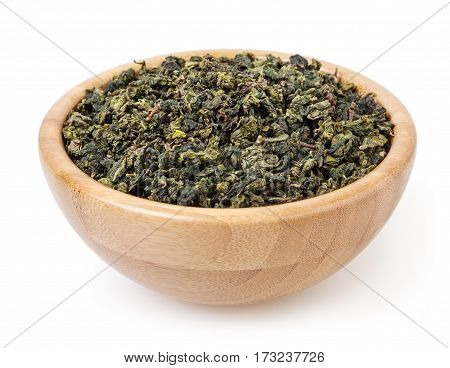 Dry green oolong tea in wooden bowl isolated on white background with clipping path
