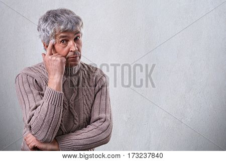 A handsome elderly man with wrinkles dressed in sweater having sad and thoughtful expression holding his finger on his temple standing near white wall with copyspace. Wise looking senior man