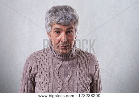 A horizontal portrait of senior handsome man standing against white wall wearing sweater looking with astonishment into camera. People emotions feelings astonishment wonder amazement