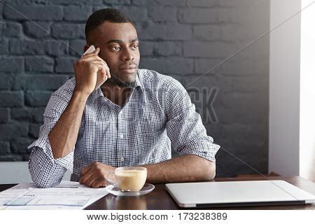 Successful African Businessman In Shirt With Rolled Up Sleeves Having Phone Call With His Partner Wh