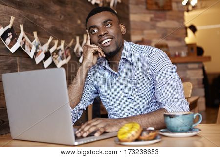 Cheerful Young African Student In Formal Shirt Thinking What To Comment On Beautiful Girl's Picture