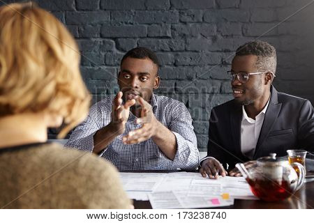 Unrecognizable Woman Candidate Sitting In Front Of Two African-american Employers During Job Intervi