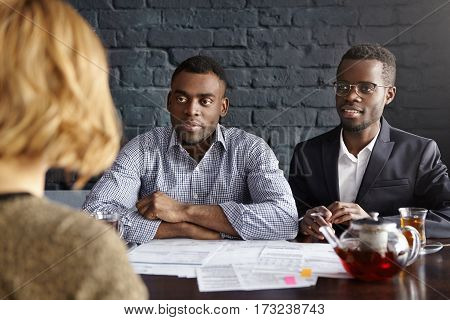 Welcome On Board. Two Handsome Dark-skinned Hr Managers Having Conversation With Unrecognizable Fema