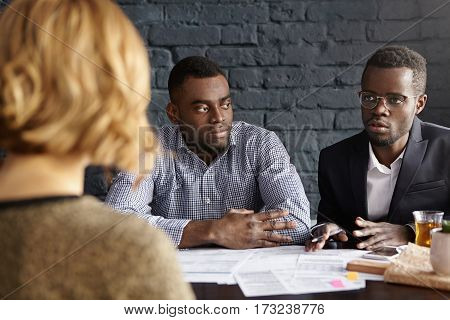 People, And Career Concept. Two Sad Dark-skinned Executives Having Meeting With Unrecognizable Femal