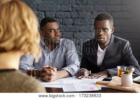 Two Attractive African-american Businessmen In Formal Wear Sitting At Office Desk With Papers, Condu
