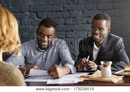Two Dark-skinned Employers Interviewing Young Woman With Fair Hair During Job Interview. Recruiting
