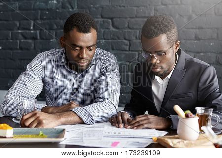 Business, Teamwork, Cooperation And Partnership Concept. Two Serious And Concentrated African-americ