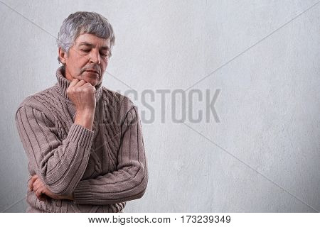 Pensive sad mature man holding his hand under his chin looking down with unhappy expression thinking about something. Thoughtful elderly man isolated over white wall with copyspace