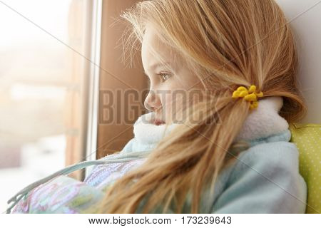 Sad Little Girl In Warm Clothes Sitting Alone On Windowsill, Looking Out Window, Watching Children P