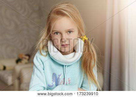 Indoor Shot Of Cute Blonde Little Girl Of European Appearance Wearing Her Hair In Messy Ponytail Pos
