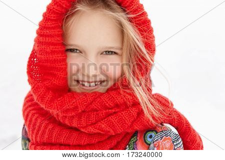 Outdoor Shot Of Cute Little Girl Of Caucasian Appearance Wearing Red Knitted Wrap Scarf, Smiling Hap