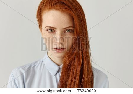 Female student or office worker with freckles and loose ginger hair wearing shirt looking at camera with serious expression posing isolated at white studio wall with copy space for your content