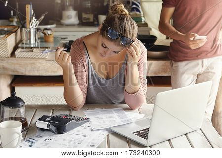 Financial Troubles And Economic Crisis. Indoor Shot Of Young Casual Housewife Reviewing Family Finan