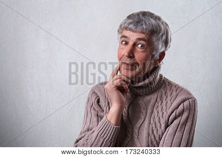 Finding perfect solution. Mature handsome man with gray hair and wrinkles holding his finger on cheek looking thoughtful and having mysterious expression while standing against white background