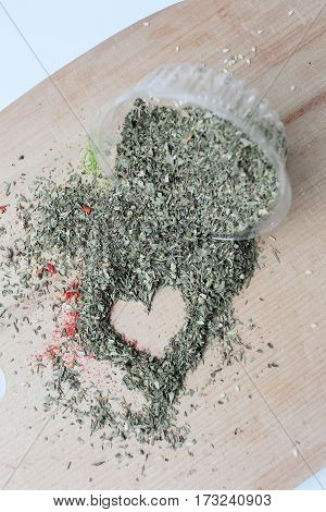 Spices scattered in the shape of a heart on a wooden background next to a jar with spices. Suitable for lighting the love and cooking.