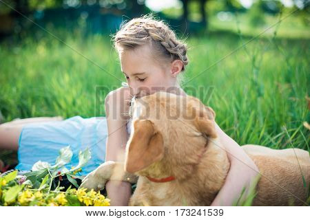girl with a dog lying on the grass in the garden on a sunny summer day