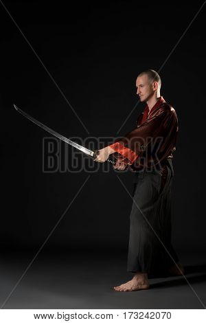 Young man in national chinese costume posing with sword in studio