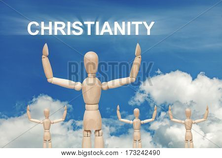 Wooden dummy puppet on sky background with text CHRISTIANITY. Abstract conceptual image