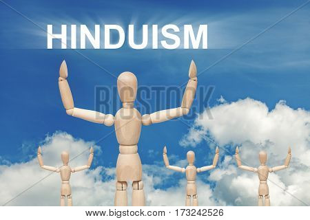 Wooden dummy puppet on sky background with text HINDUISM. Abstract conceptual image