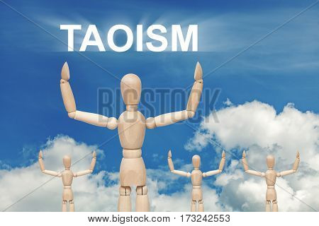 Wooden dummy puppet on sky background with text TAOISM. Abstract conceptual image poster