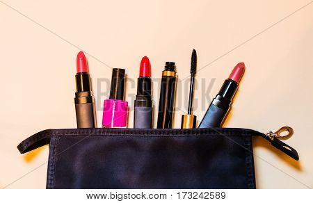 Make-up bag with cosmetic products spilling out to beige background