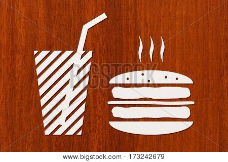 Paper burger and beverage inside on wooden background fastfood concept. Abstract food conceptual image