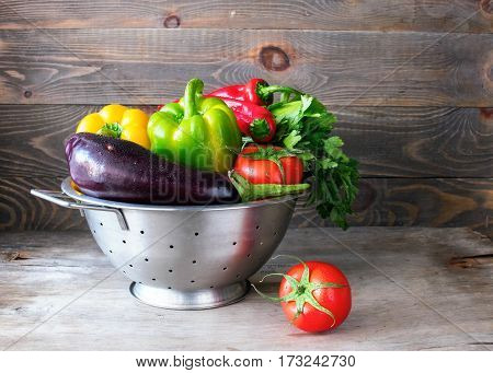 Fresh vegetables tomato zucchini eggplant sweet pepper hot pepper metal colander wooden table .A healthy way of life. Dark background copy space close-up