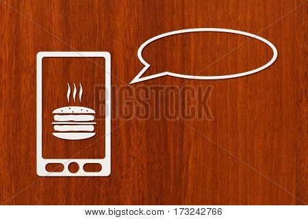 Paper tablet or smartphone with burger on screen and speech bubble copyspace dark wooden background. Abstract conceptual image