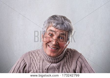 A positive cheerful kind mature man wearing glasses looking kindly into camera having gentle smile. Smiling senior man while standing over white background. Emotions and feelings concept