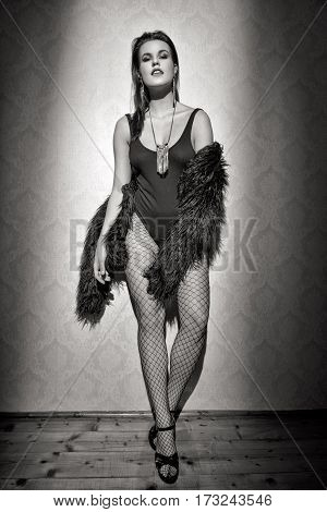 Fashionable sexy woman posing at vintage wall black and white